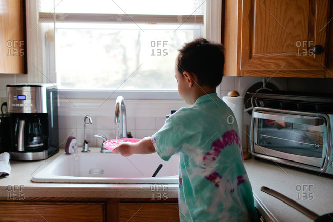 Young boy washing a plate in the sink