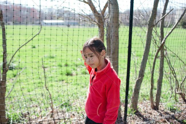 Girl walking along fence in spring