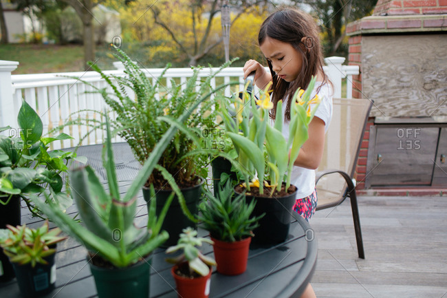 Young girl taking care of plants on backyard deck