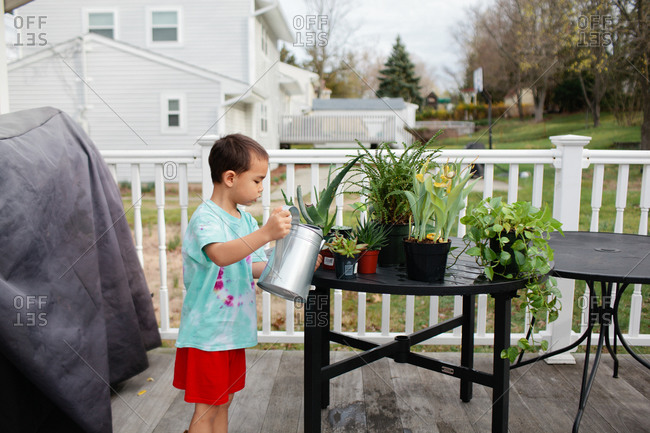 Young boy watering plants on backyard deck