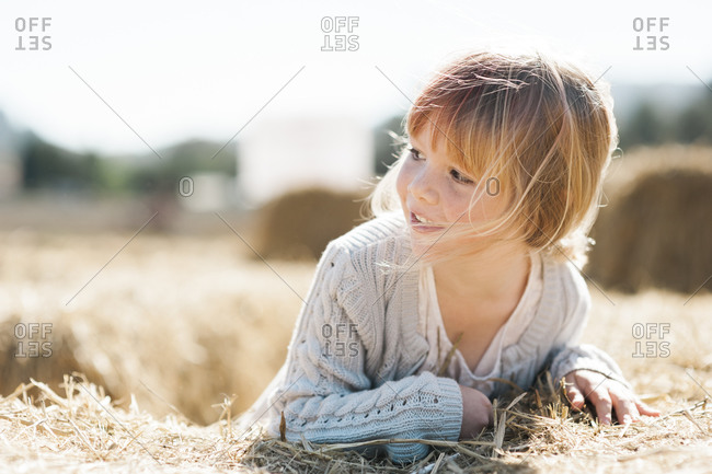 Young girl playing on a bale of hay