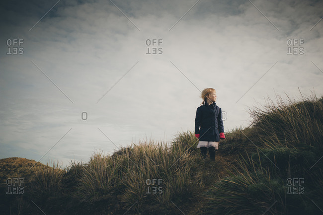 Young girl standing on grassy hillside under cloudy sky