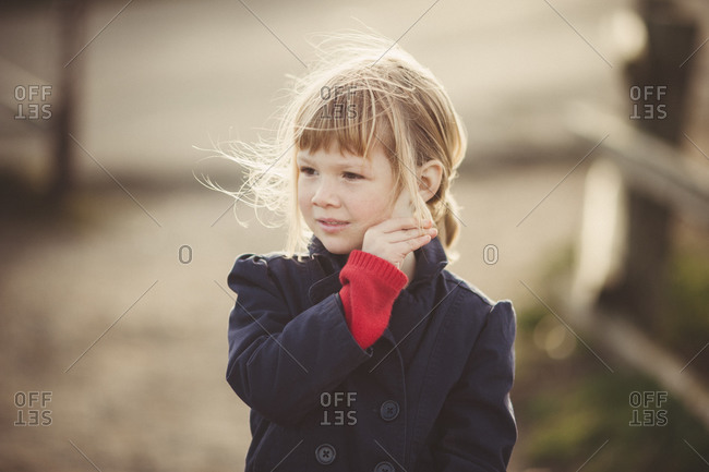 Young girl in blue coat fixes her hair