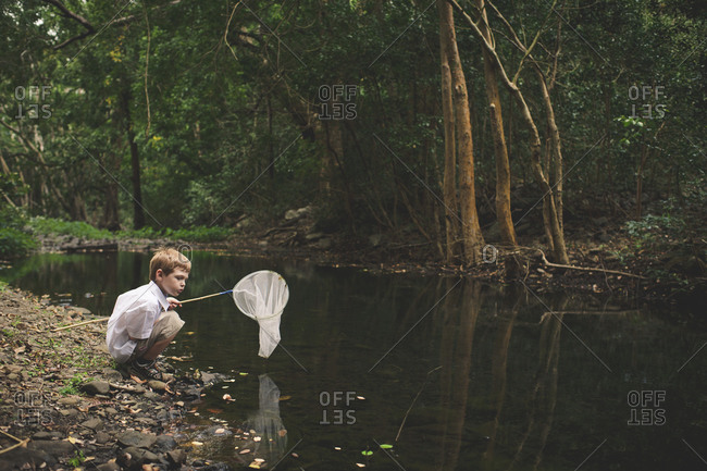 Boy with fishing net squatting at edge of stream
