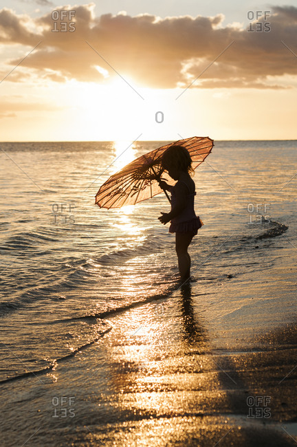 Silhouette of young girl with umbrella on beach
