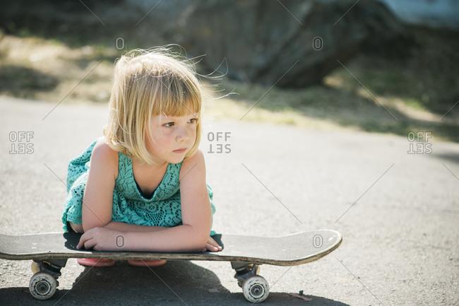 Little girl resting on a skateboard in street