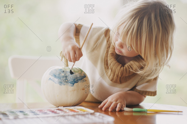 Young girl decorating a white pumpkin with paint