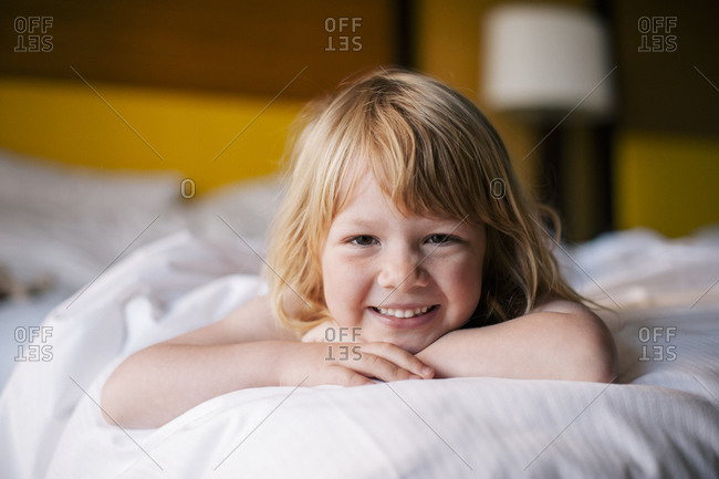 Portrait of young girl resting on bed