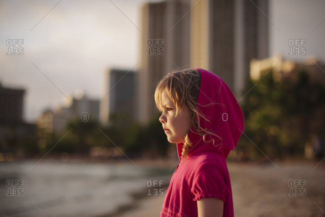 Girl in hooded dress standing on beach at sunset