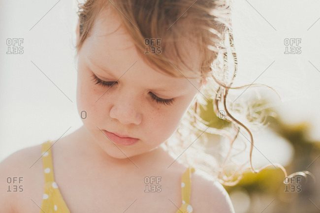 Close-up portrait of young girl with wet hair on beach