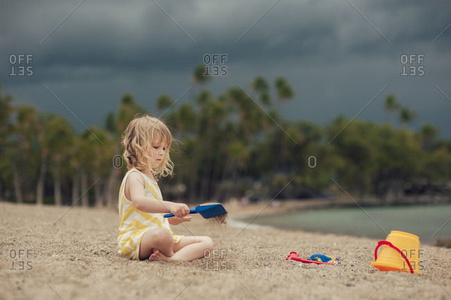 Toddler girl playing on sandy beach under stormy skies