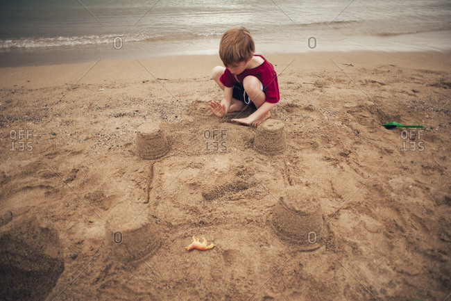 Elevated view of young boy building sand castle on beach