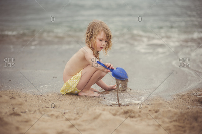 Young girl digging with shovel on beach