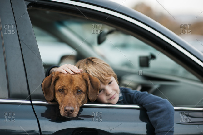 Boy and dog looking out car window