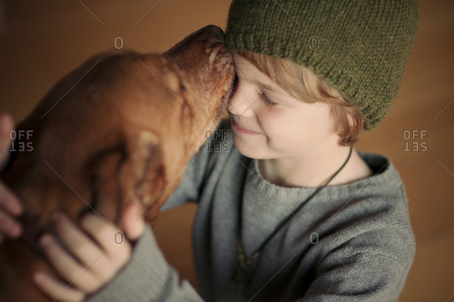 Young boy receiving a kiss from his dog
