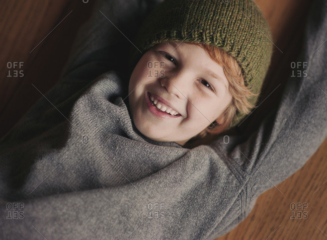 Portrait of young boy in knit hat lying on wood floor