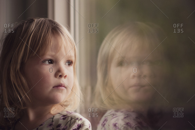 Young girl gazing out window