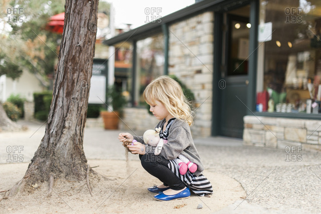 Young girl playing with pinecone on sidewalk