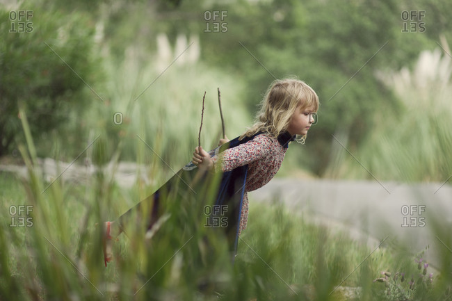Toddler girl in cape playing with two sticks in grass