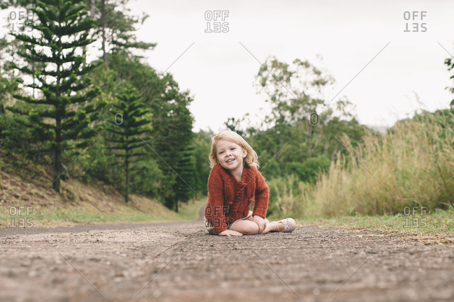 Portrait of young girl sitting on a rural road