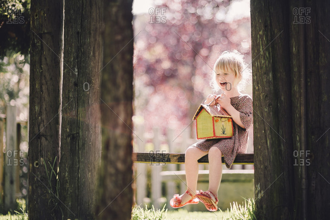 Laughing young girl sitting on bench with toy house