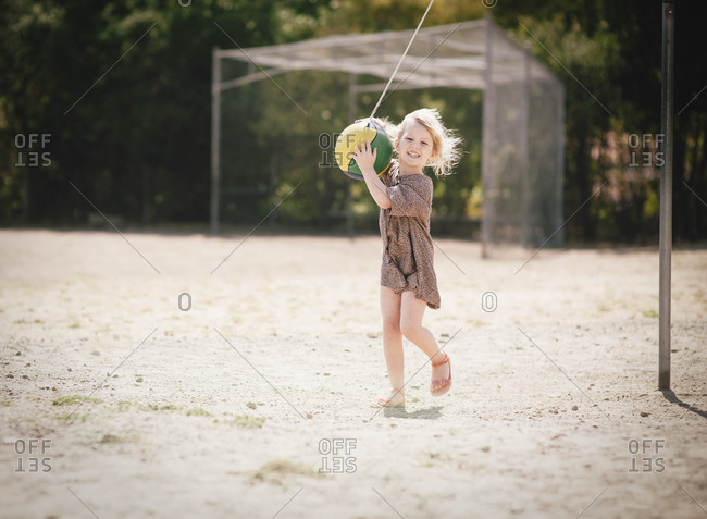 Young girl playing with tetherball on playground