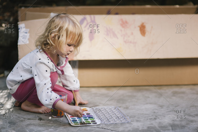 Young girl painting cardboard box with watercolors