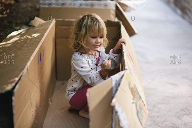 Young girl painting a cardboard box