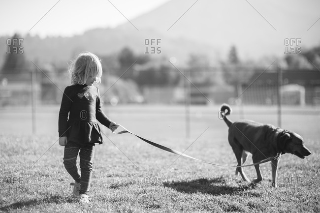 Young girl walking her dog on a leash in field