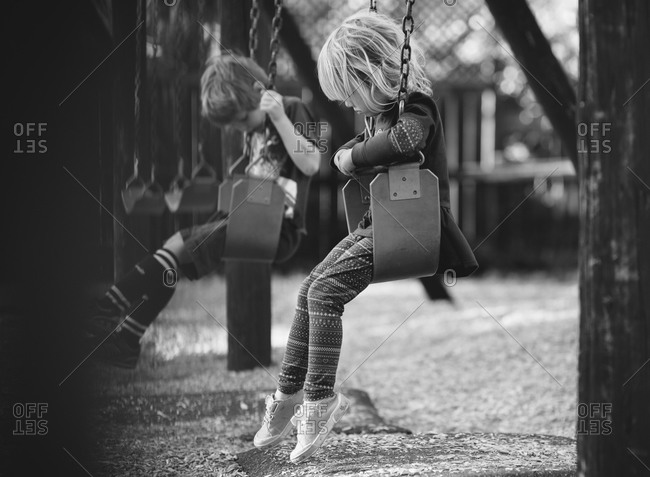 Boy and girl on swings at playground