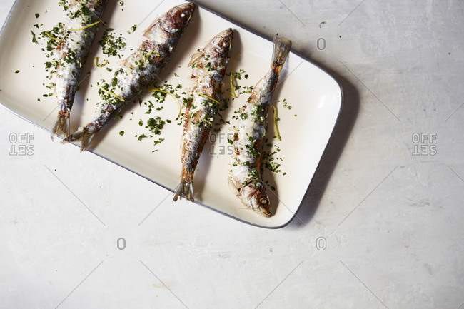 Fresh, whole cooked sardines served on a plate