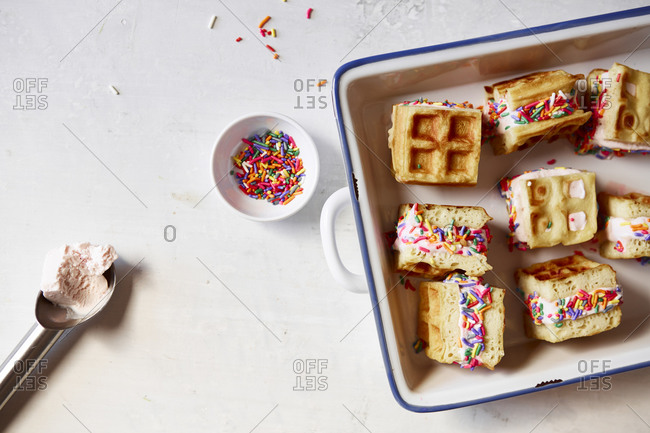 Ice cream sandwiches made with waffles, vanilla ice cream, and sprinkles