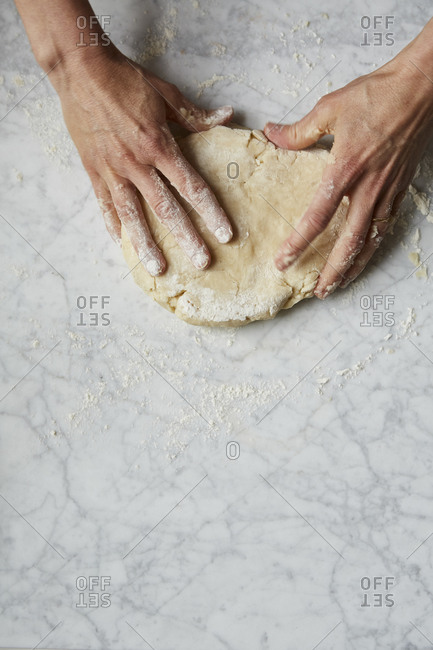 Baker working with dough to make a pie crust