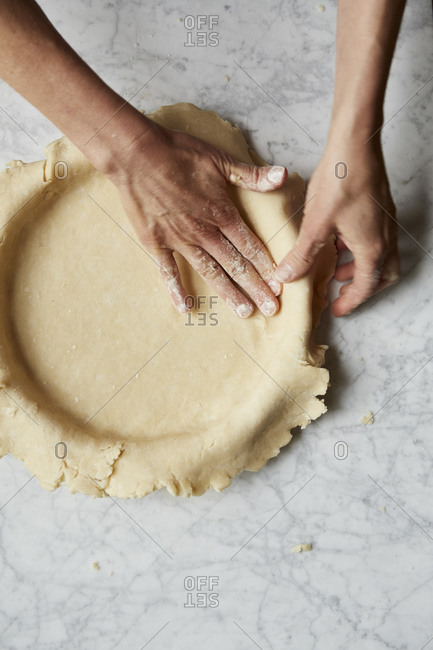 Baker pressing a rolled pie crust into a bowl