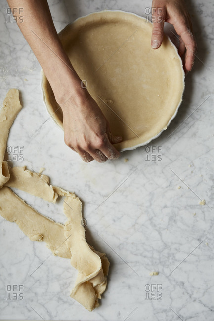 Baker trimming off the excess dough from a pie crust pressed into a bowl