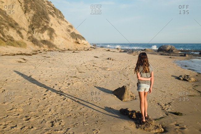 Girl standing on beach stone