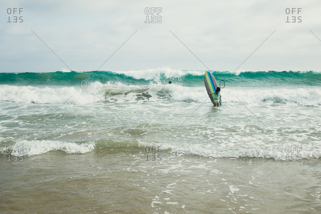 Girl carrying surfboard in sea