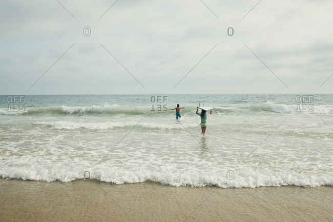 Kids in sea waves with boards