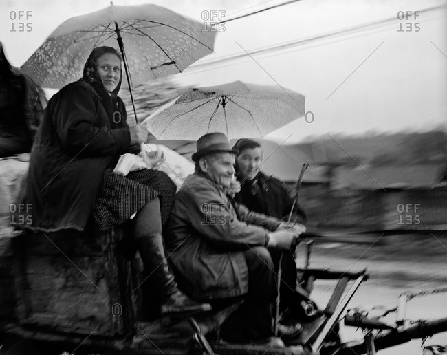 Romania - November 14, 2008: Women traveling with umbrellas on a horse and cart on a country road in Maramures, Romania
