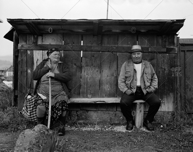 Romania - November 14, 2008: An elderly woman and man wait in a shelter during a rain storm in the rural region of Maramures, Romania