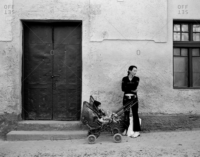 Romania - November 14, 2008: A mother standing with her child on a street in the town of Rupea, Transylvania, Romania
