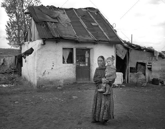 Romania - December 9, 2011: Portrait of a Roma mother and her child in a gypsy community in Copsa Mica, Transylvania, Romania
