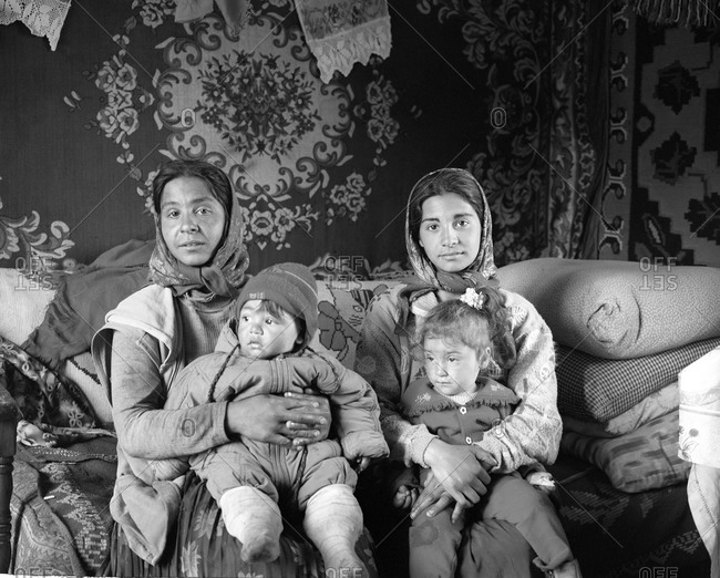 Romania - December 9, 2011: Portrait of two Roma mothers with their children in a gypsy community in Copsa Mica, Transylvania, Romania