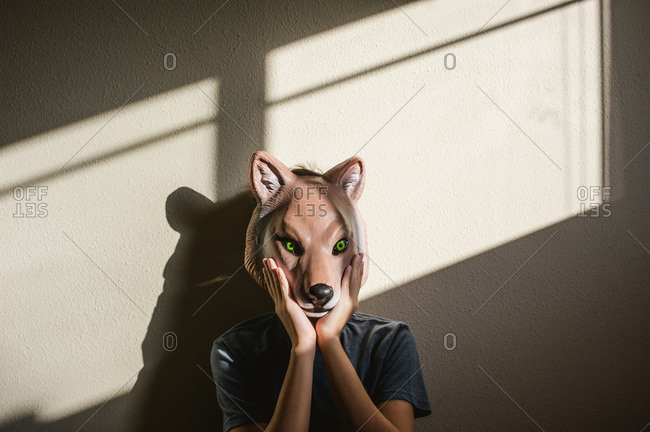 Boy holding a plastic wolf mask to his face