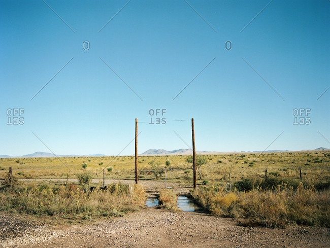 Fence gate to ranch on rural dirt road