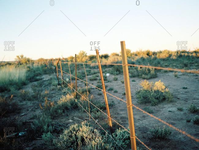 Barbed wire fence in desert landscape at dusk