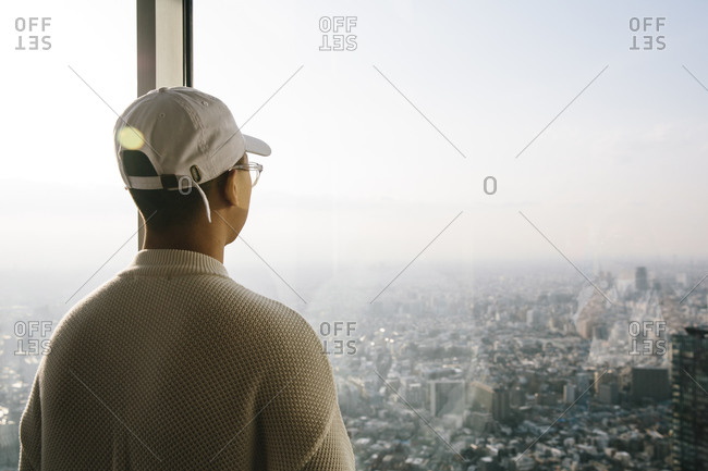 Man wearing a baseball cap standing in front of a window looking out over a city skyline