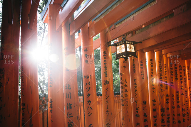 Lantern hanging from orange lacquered Torii gates in Japan