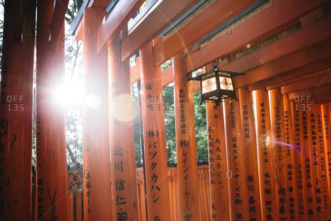 Lantern hanging from orange lacquered Torii gates in Japan