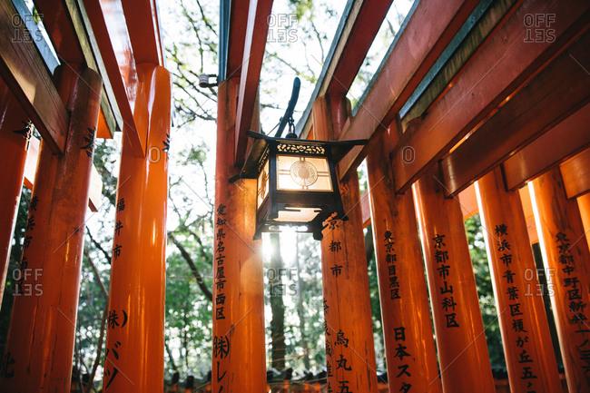 Lantern hanging from orange lacquered Torii gates